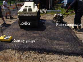 Figure 9. Photograph. Construction of asphalt overlay specimens utilizing a nuclear density gauge to ensure adequate compaction.