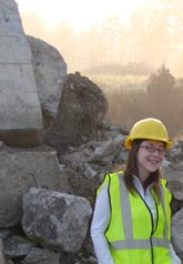 This is a photo of Jennifer Nicks. She is standing in front of a pile of rubble and is wearing a white shirt, glasses, safety vest, and hard hat.