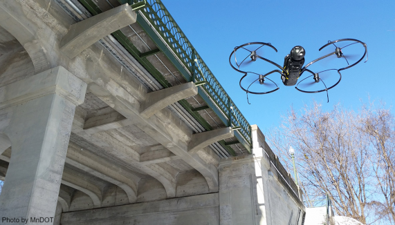 Flying drone inspects bridge improves transportation performance by advancing innovation.