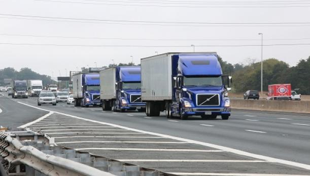A photo showing three trucks traveling on a multi-lane highway at equally spaced intervals within a platoon.