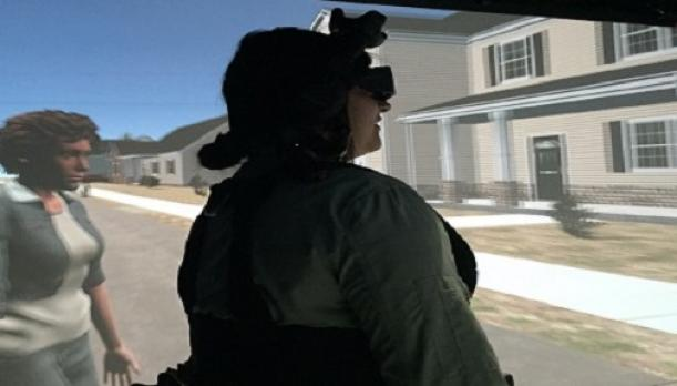 Photo of a woman wearing a virtual reality head-mounted display standing before a video screen showing her simulated avatar.